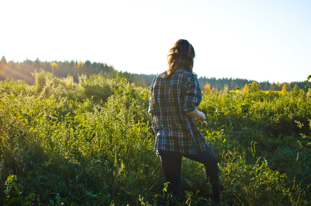 A woman in a flannel in a sunny field
