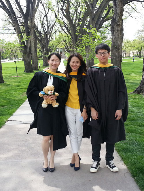 Three graduates standing outside