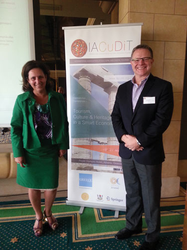 two people posing in front of a IACuDiT poster