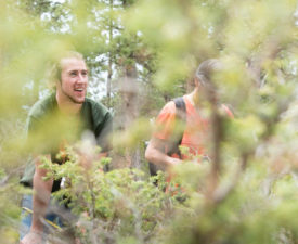 Two men viewed through a bush