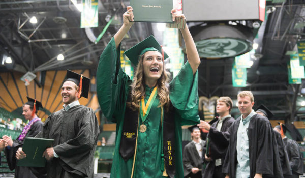 Female student in green graduation robes holding up diploma