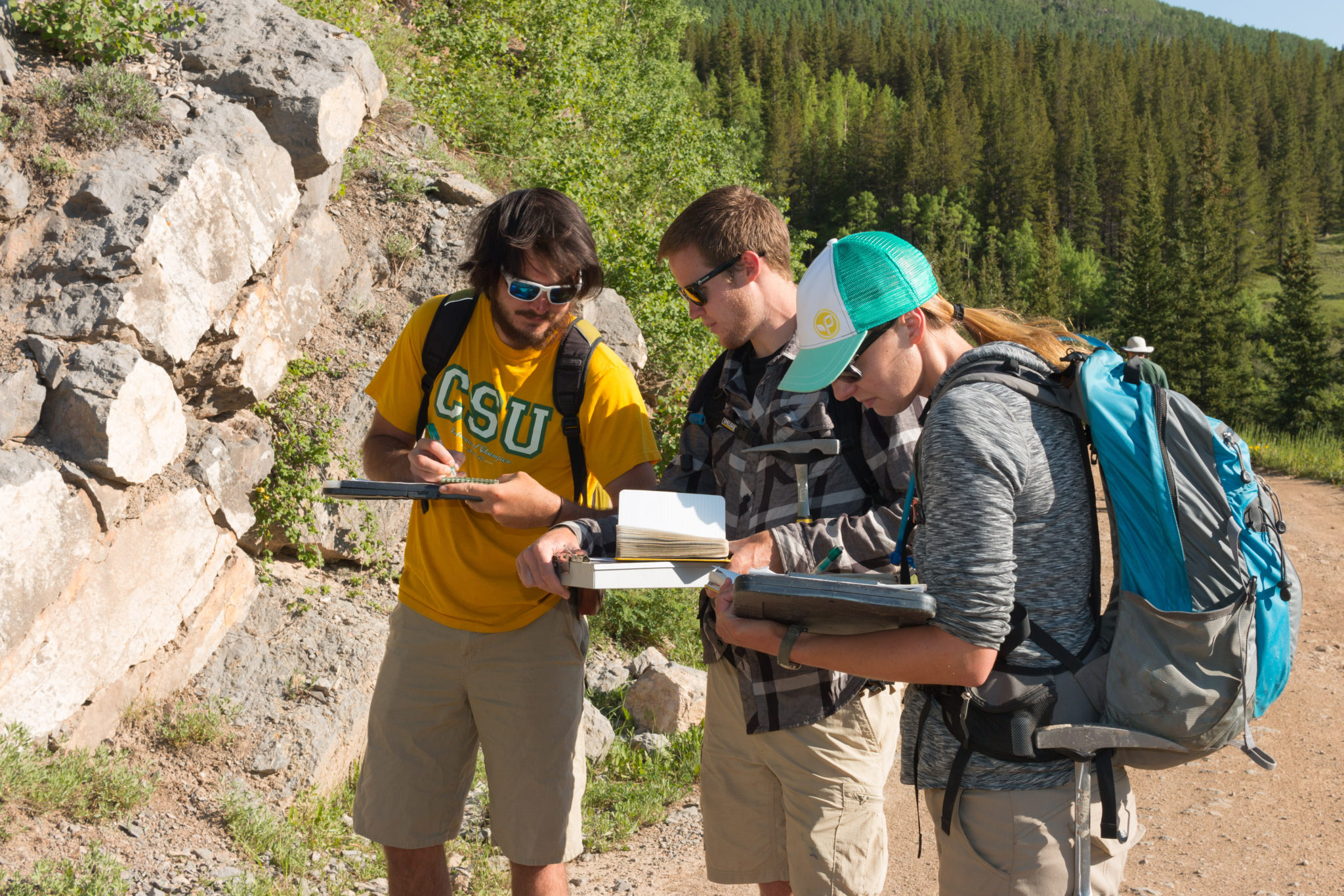 Photo of three students int he field making maps.