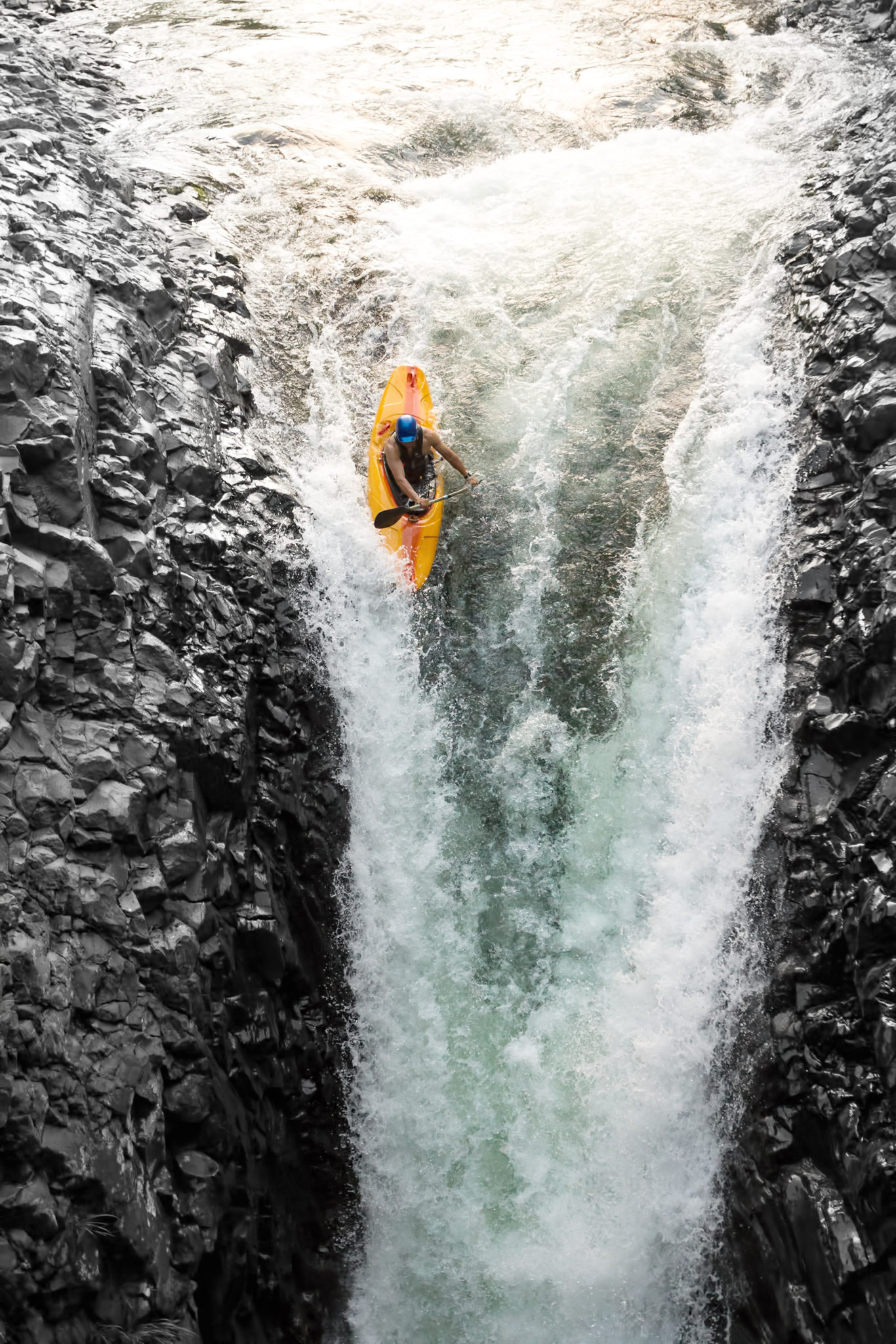 A person kayaking down a large waterfall