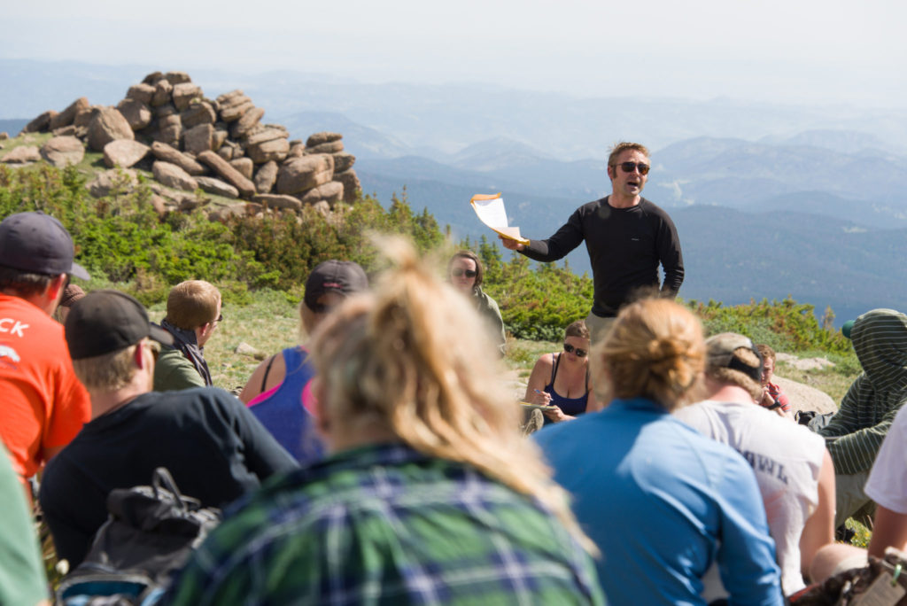 A man talking to a group of people on top of a mountain