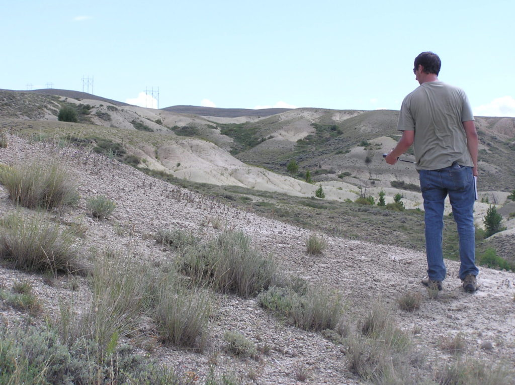 man standing on a grassy hill