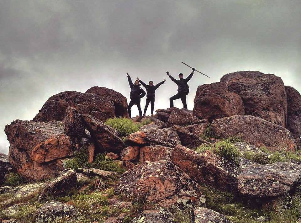 three people on top of a rocky mountain