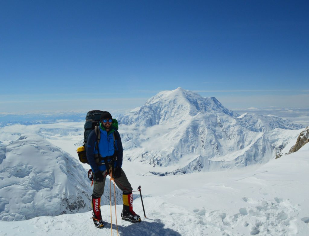 backpacker on top of a snowy mountain
