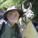 A man smiling with a llama