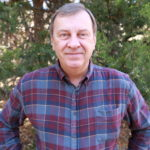 a man in blue and red plaid in the forest