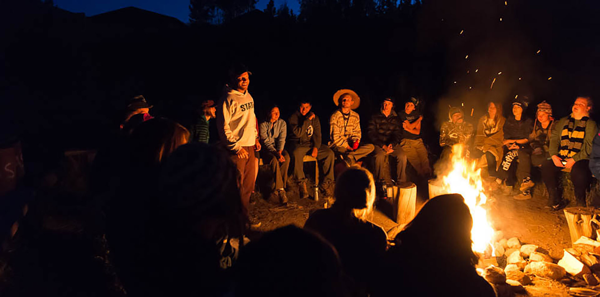 Students sitting around campfire