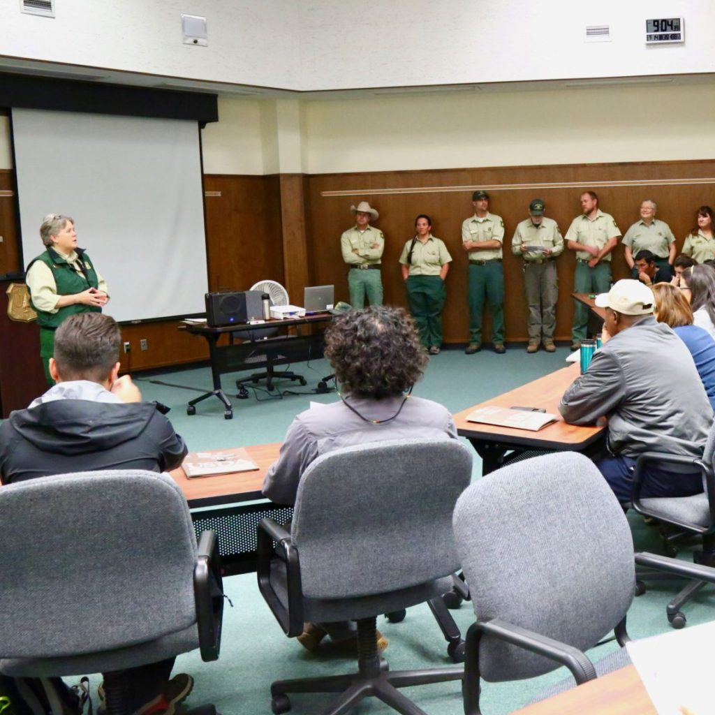 A woman giving a presentation to a group of rangers