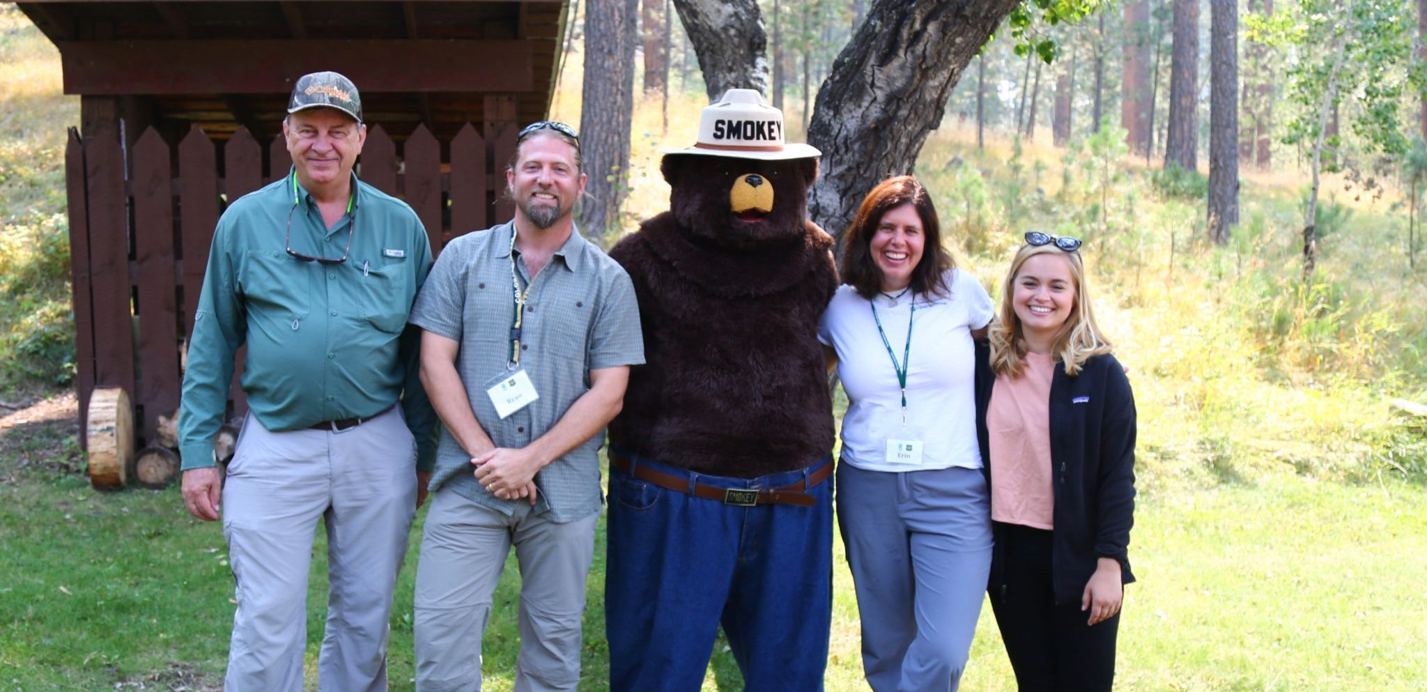 four people posing with smoky the bear in a forest