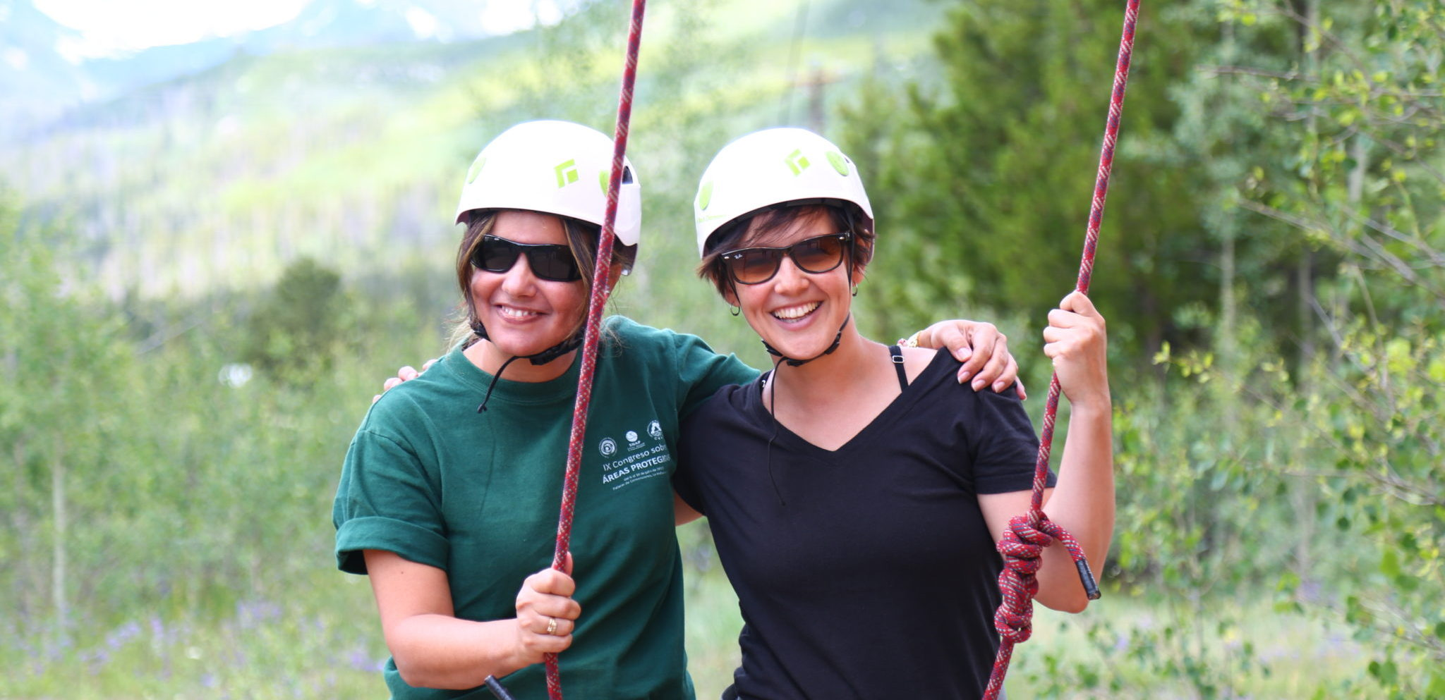 two women standing in the forest with rock climbing ropes
