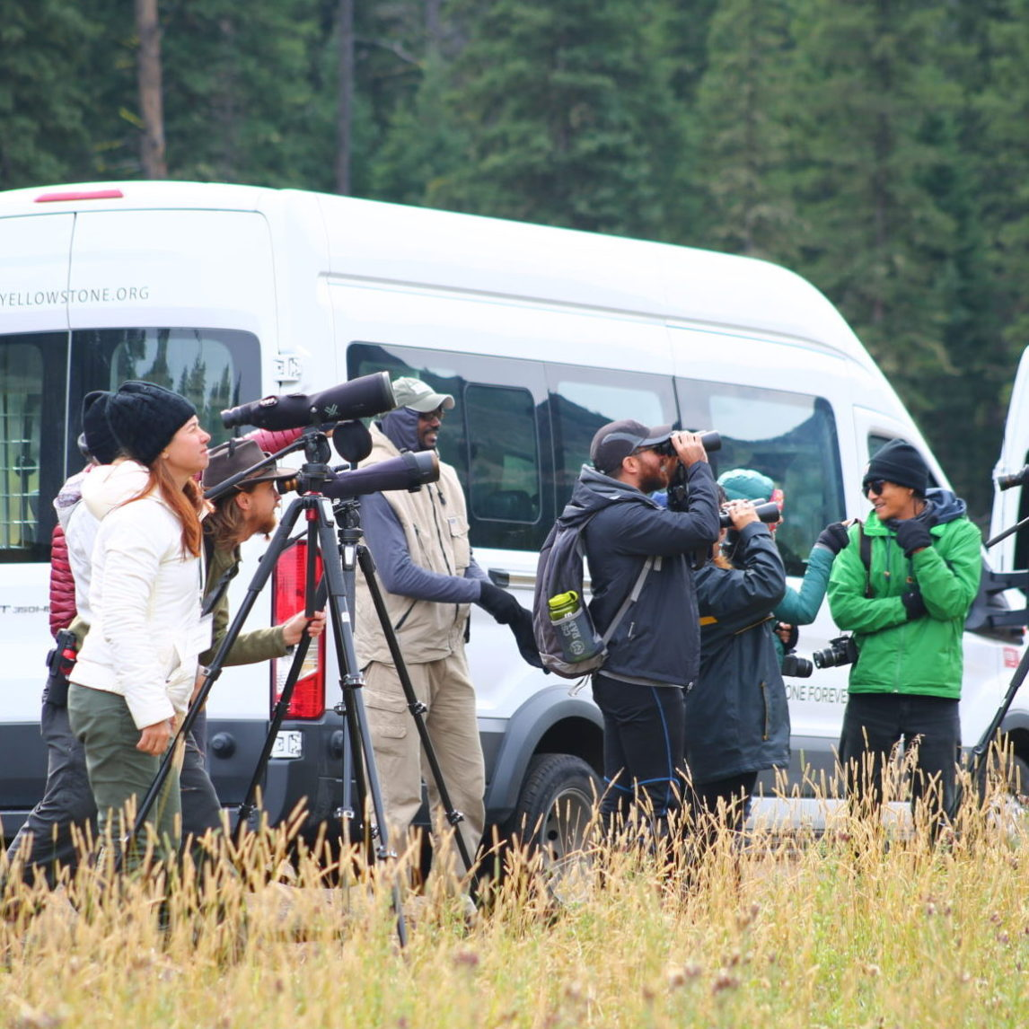 A group of photographers beside a bus