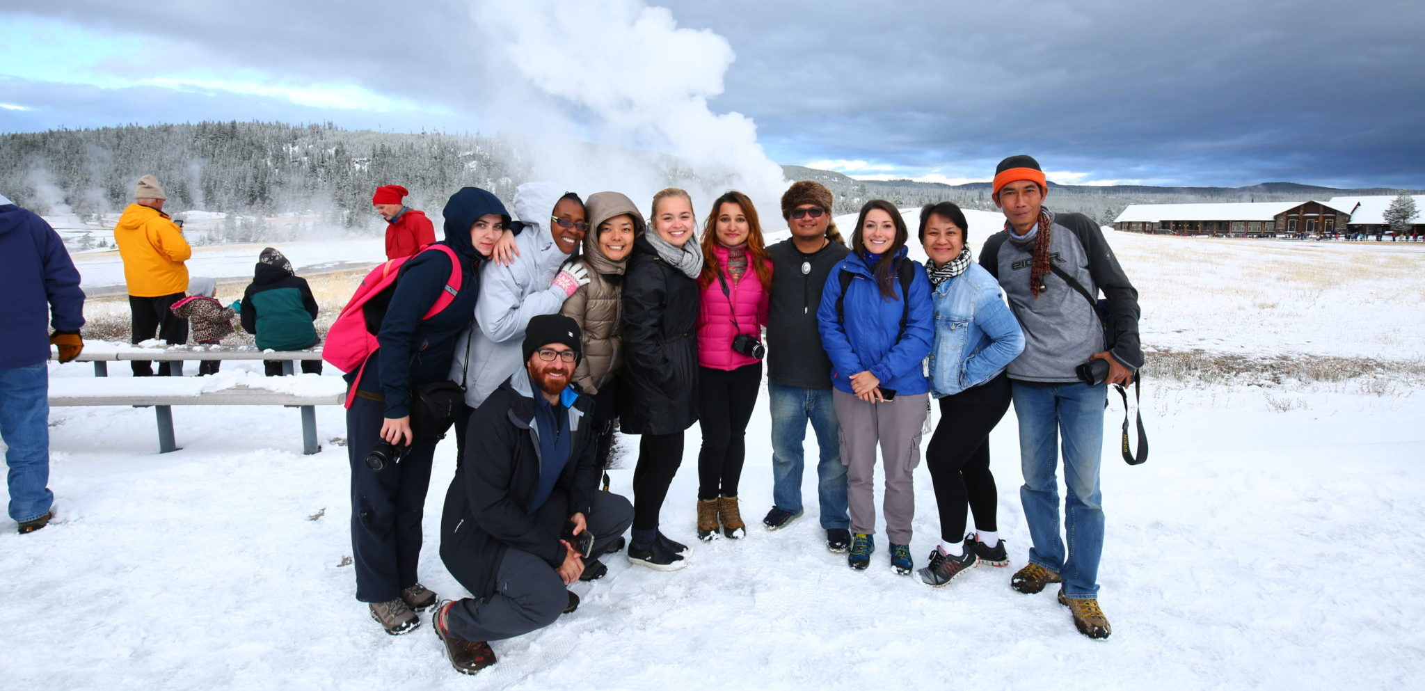 a group of people in a snowy field with a steam vent behind them