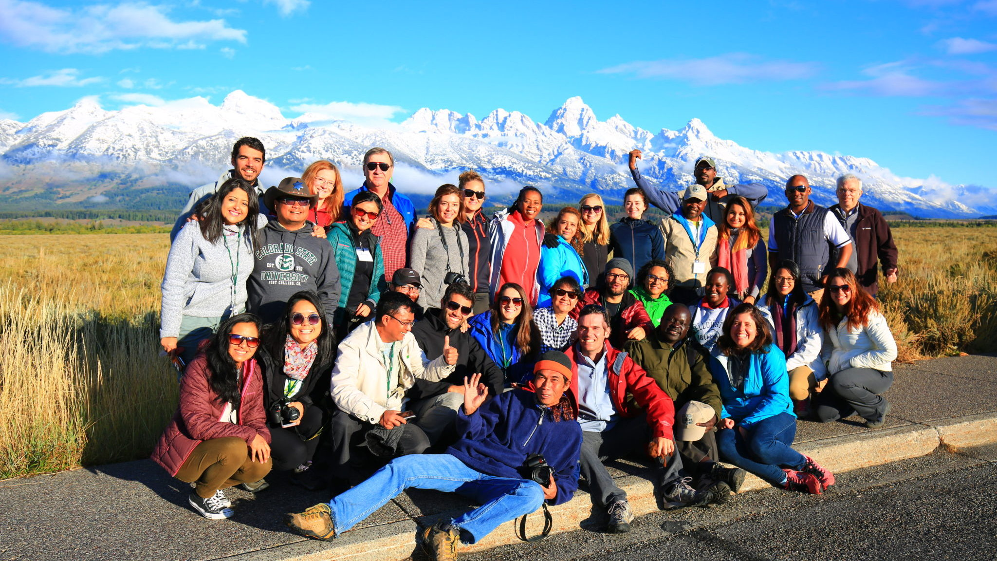 A group of people in front of snowy mountains