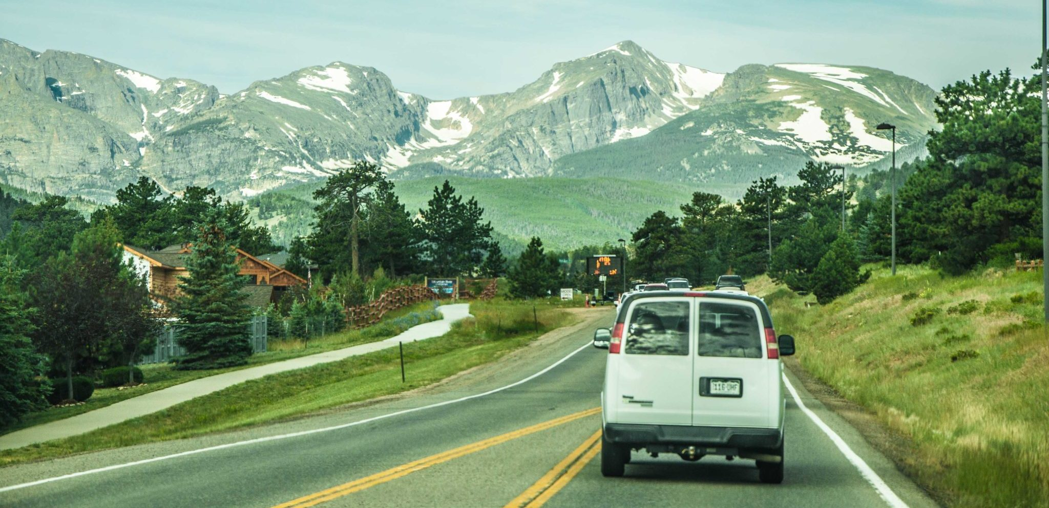 white van driving toward the mountains