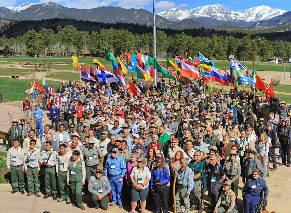 a large group of people standing in front of the mountains
