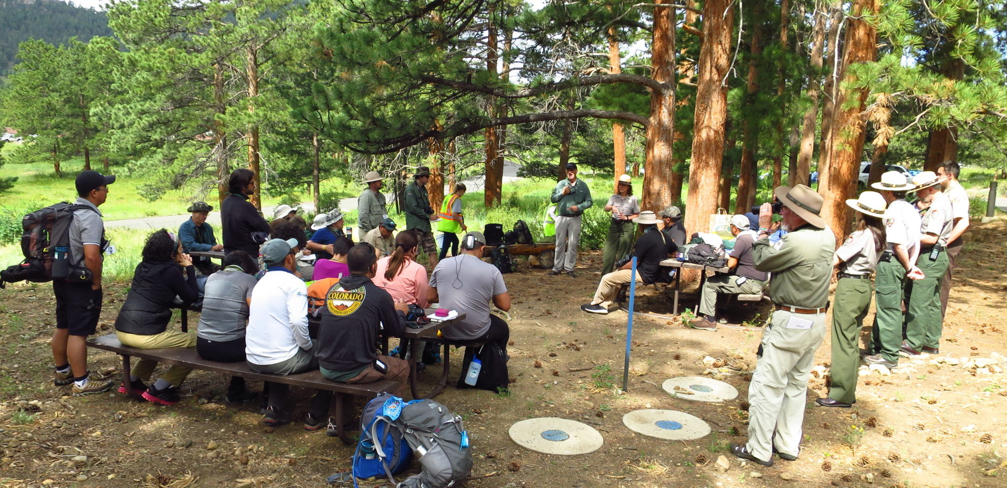 a bunch of people listening to a speaker in a camp ground
