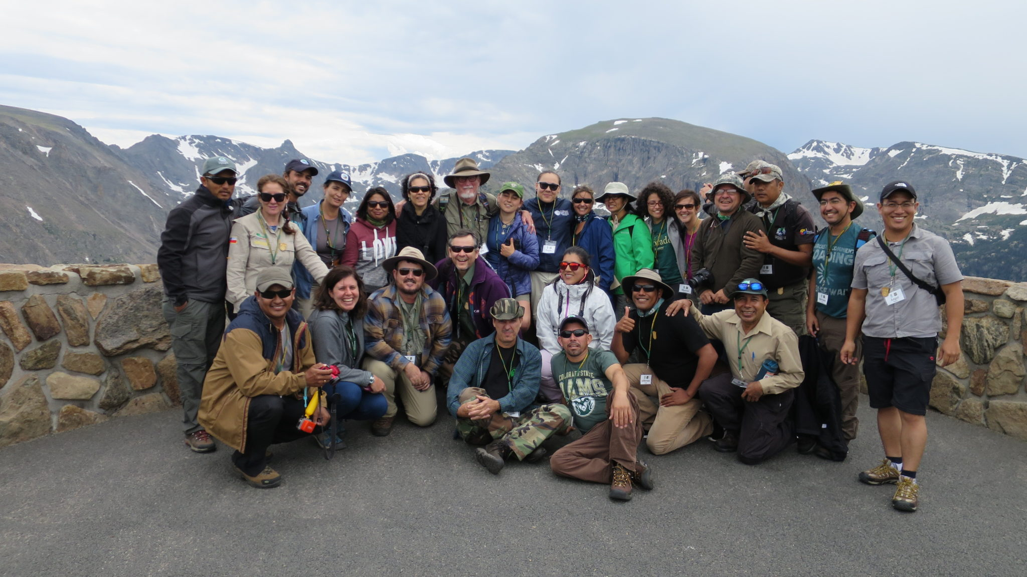 a group of people standing in front of mountains