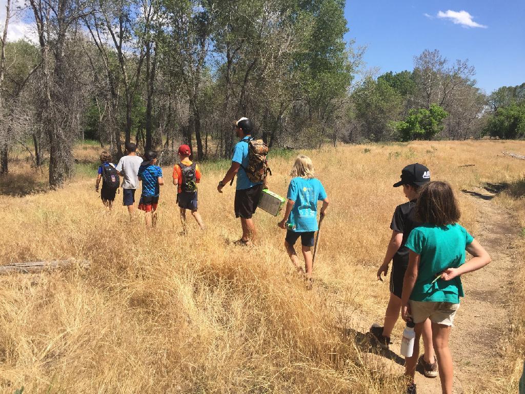 Several children walk with an instructor through a grassland