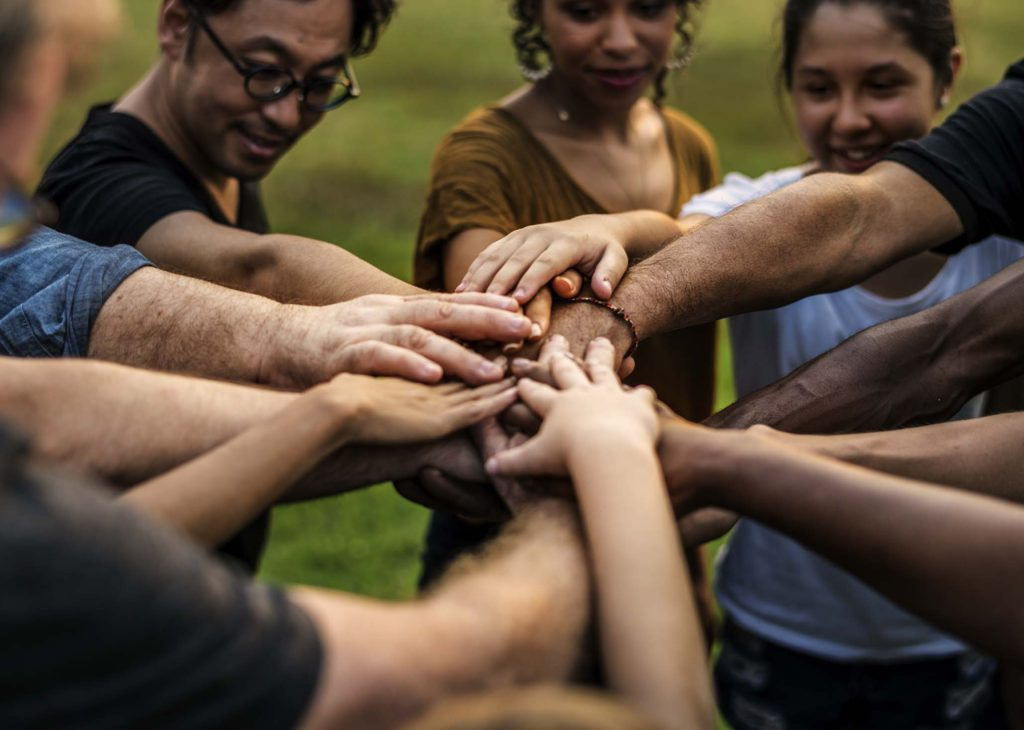 Group of diverse persons with their hands united in the center of the group