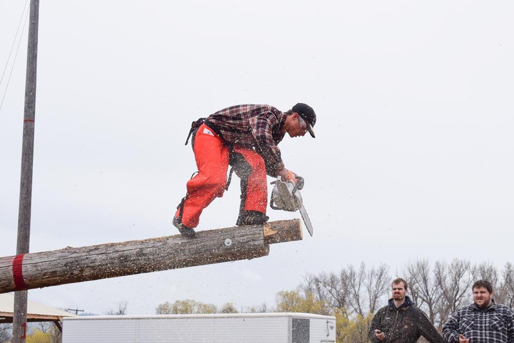 CSU student cuts log with chainsaw