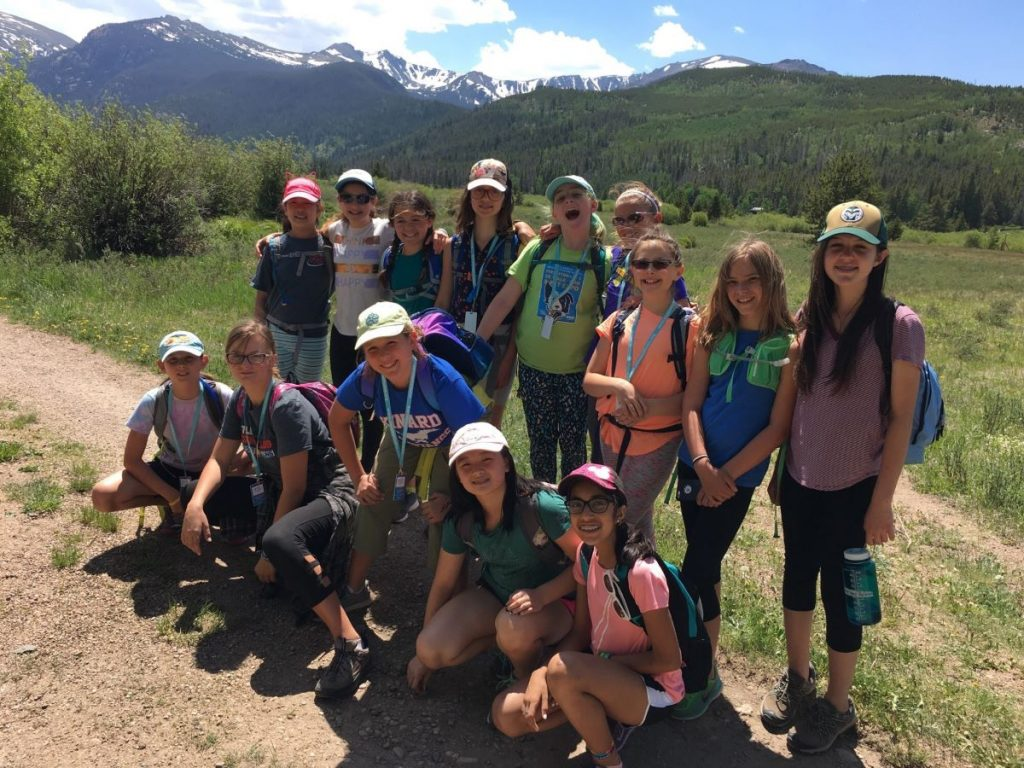A group of girls on a trail in the mountains