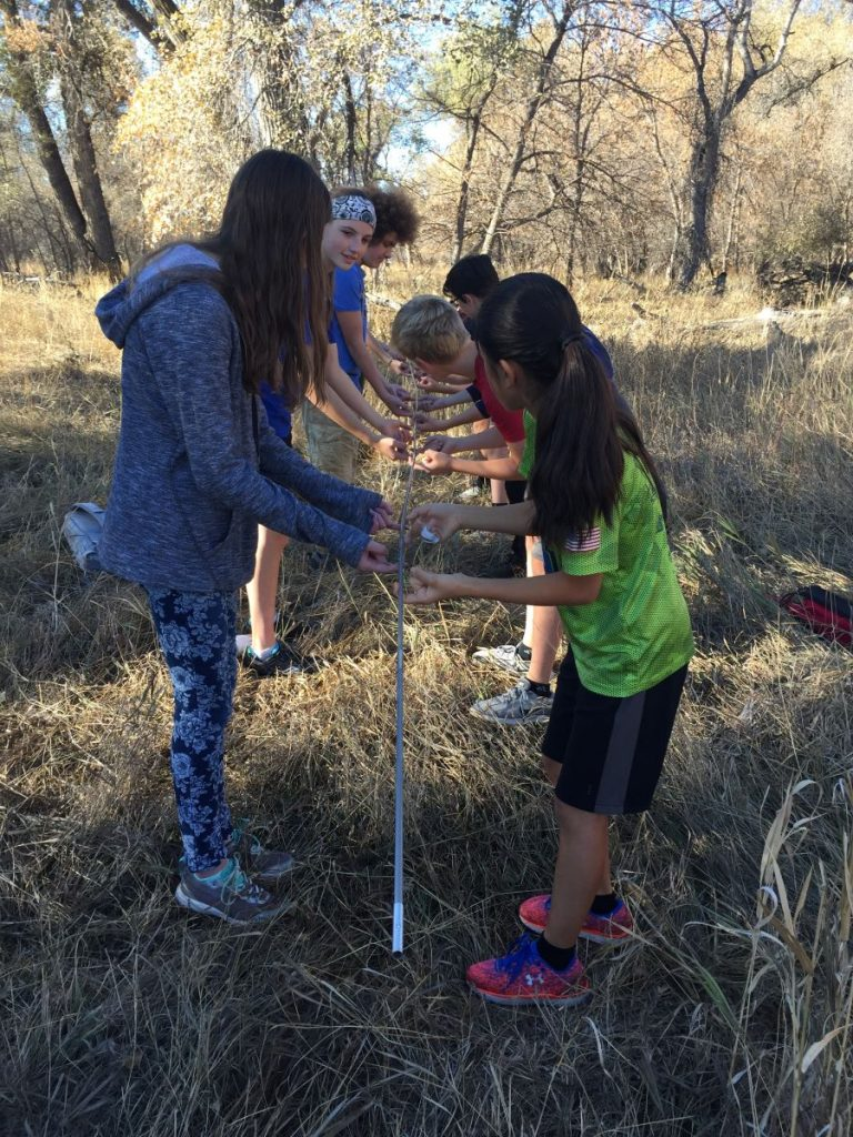 Several kids hold a tent pole