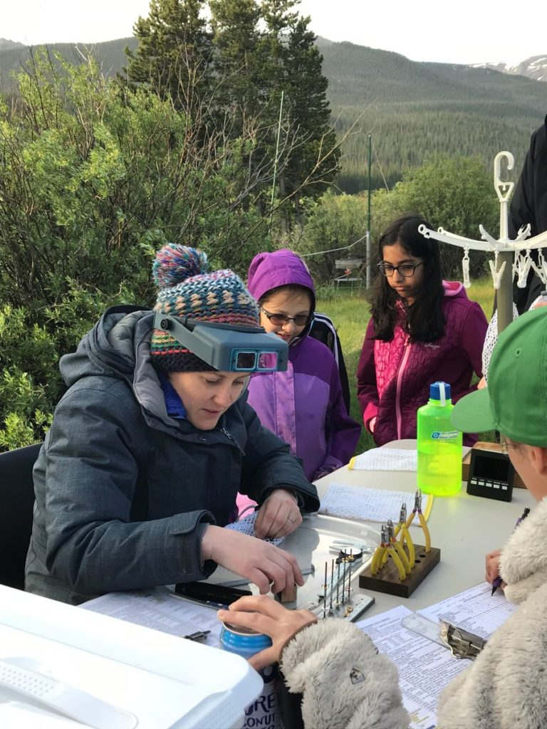 Children assist with bird banding
