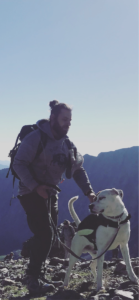 Sully hikes on a mountain with his dog
