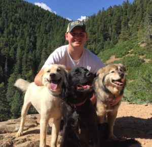 Zach poses with three dogs, mountains in the background